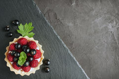 Tartlets with raspberries and black currants. On a slate board background Stock Photos