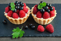 Tartlets with raspberries and currants. On a slate board background Stock Photos