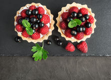 Tartlets with raspberries and currants. On a slate board background Royalty Free Stock Images