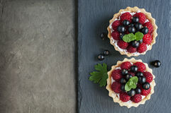 Tartlets with raspberries and currants. On a slate board background Stock Images