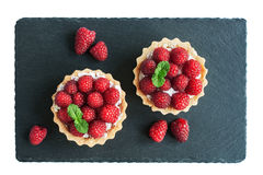 Tartlets with raspberries. On a slate board Royalty Free Stock Photos