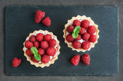 Tartlets with raspberries. On a slate board background Stock Image