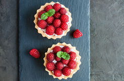 Tartlets with raspberries. On a slate board background Royalty Free Stock Image