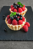 Tartlets with raspberries. On a slate board background Royalty Free Stock Photography