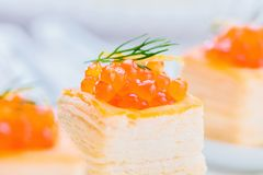 Tartlets with red caviar on white plate royalty free stock image