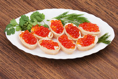 Tartlets with red caviar on wooden background. Royalty Free Stock Image