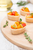 Tartlets with roasted vegetables and thyme on board Stock Photos