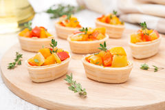 Tartlets with roasted vegetables and thyme on a wooden board Royalty Free Stock Image