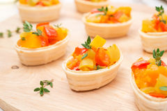 Tartlets with roasted vegetables and thyme on a wooden board Stock Photography
