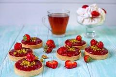 Tartlets rojos brillantes de los pasteles, adornados con las fresas y los pistachos en un fondo de madera azul Imagen de archivo