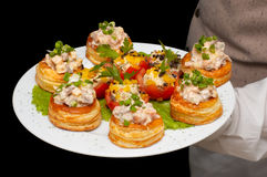 Tartlets with salad on dish. Held by waiter Royalty Free Stock Images