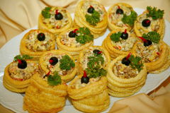 Tartlets with salad on dish. Mini quiches. Plate of many mini bite size quiche appetizers. Tartlets with salad on dish, held by waiter. Salty mini tartlets Stock Photos