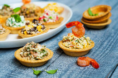 Tartlets with salads and shrimps on a white plate on wooden table Stock Photos