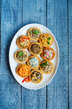Tartlets with salads and shrimps on a white plate on wooden table Stock Image
