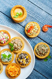 Tartlets with salads and shrimps on a white plate on wooden table Royalty Free Stock Image