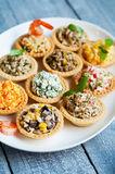 Tartlets with salads and shrimps on a white plate on wooden table Royalty Free Stock Photography