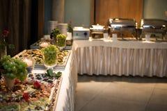 Tartlets, Salate und Fruchtkorb mit Apfel, Orange, Trauben und Saft auf einem Hintergrund (Fokus auf Tartlets) Stockbild