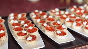 Tartlets som fylls med den röda kaviaren och gräddost på vita plattor stock video