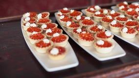 Tartlets som fylls med den röda kaviaren och gräddost på vita plattor lager videofilmer
