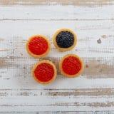 Tartlets som fylls med den röda och svarta kaviaren mot lantlig träbakgrund Royaltyfria Bilder