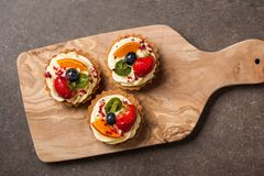 Tartlets with various berries on wooden cutting board. Top view Stock Images