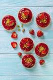 Tartlets vermelhos brilhantes da pastelaria, decorados com morangos e pistaches em um fundo de madeira azul Fotos de Stock