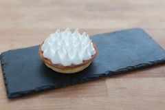 Tartlets with whipped cream on black ceramic stand Royalty Free Stock Images