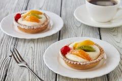 Tartlets z śmietanką i owoc, pomarańcze, kiwi, wiśnia Fotografia Stock