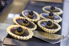 Tartlets z czekoladowym plombowaniem i winogrona na czarnej tacy obrazy stock