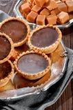 Tartlets z czekoladowymi podsadzkowymi zakończenia i toffee karmelu kawałkami na srebnym rocznika talerzu na drewnianym stołowym  obraz royalty free