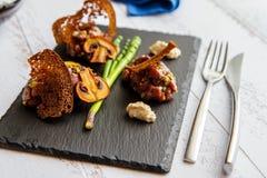 Tartre, champignons et pain grillé sur la pierre noire image stock