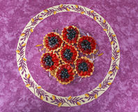 Tarts with berries on colorful tablecloth Stock Images