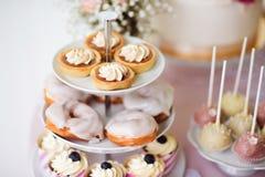 Tarts, kremowi chuchy, babeczki na cakestand Tortów wystrzały Zdjęcia Stock