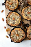Tarts with nuts and raisins filling on a wooden board. Stock Photography