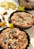 Tarts with nuts and raisins filling on a wooden board. Royalty Free Stock Photos