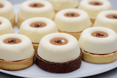 Tarts with vanilla pudding and coffee cream. On white plate stock photography