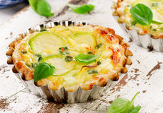 Tarts with zucchini and cheese on white wooden background. Royalty Free Stock Image