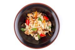 Tarwenoedels met varkensvlees en groenten onder teriyakisaus, op witte achtergrond wordt geïsoleerd die Tarwenoedels in een zwart royalty-vrije stock fotografie