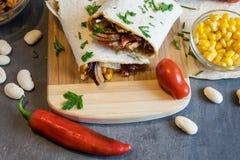 Tarwetortilla met een mengsel van varkensvlees, bonen, rood ui en graan stock afbeeldingen