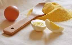 Tas de farine de maïs, de cuillère en bois et d'oeufs Image libre de droits