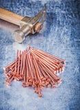 Tas de marteau de griffe de vintage des clous de cuivre de construction sur l'éraflure Photographie stock