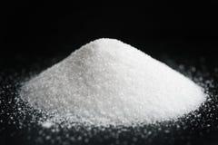 Tas de petit sel supplémentaire sur le fond noir images stock