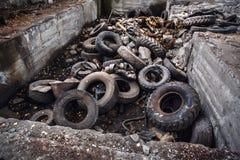 Tas de vieux pneus d'ordure de voiture, roues utilisées de déchets de camion, déchets industriels dans l'usine abandonnée Photographie stock libre de droits