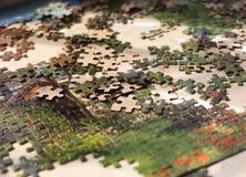 Tas des éléments colorés de puzzles sur la surface beige Photographie stock libre de droits