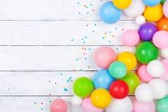 Tas des ballons et des confettis color?s sur la vue sup?rieure blanche de table Fond de f?te ou de partie Configuration plate Car photo stock