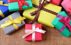 Tas des cadeaux enveloppés pour Noël ou toute autre célébration sur la toile de jute Photographie stock libre de droits