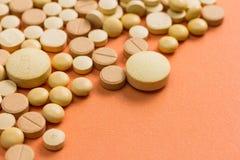 Tas des capsules beiges assorties sur la table orange photos stock