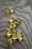 Tas des capsules d'Omega d'huile de poisson sur la table en bois Photo stock