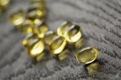 Tas des capsules d'Omega d'huile de poisson sur la table en bois Photo libre de droits
