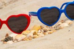 Tas des coquilles et des lunettes de soleil sur le sable à la plage Photographie stock libre de droits